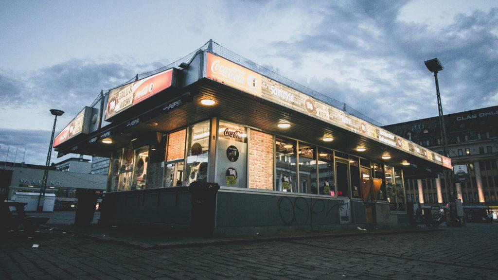 A brightly lit kiosk in a dark urban setting.