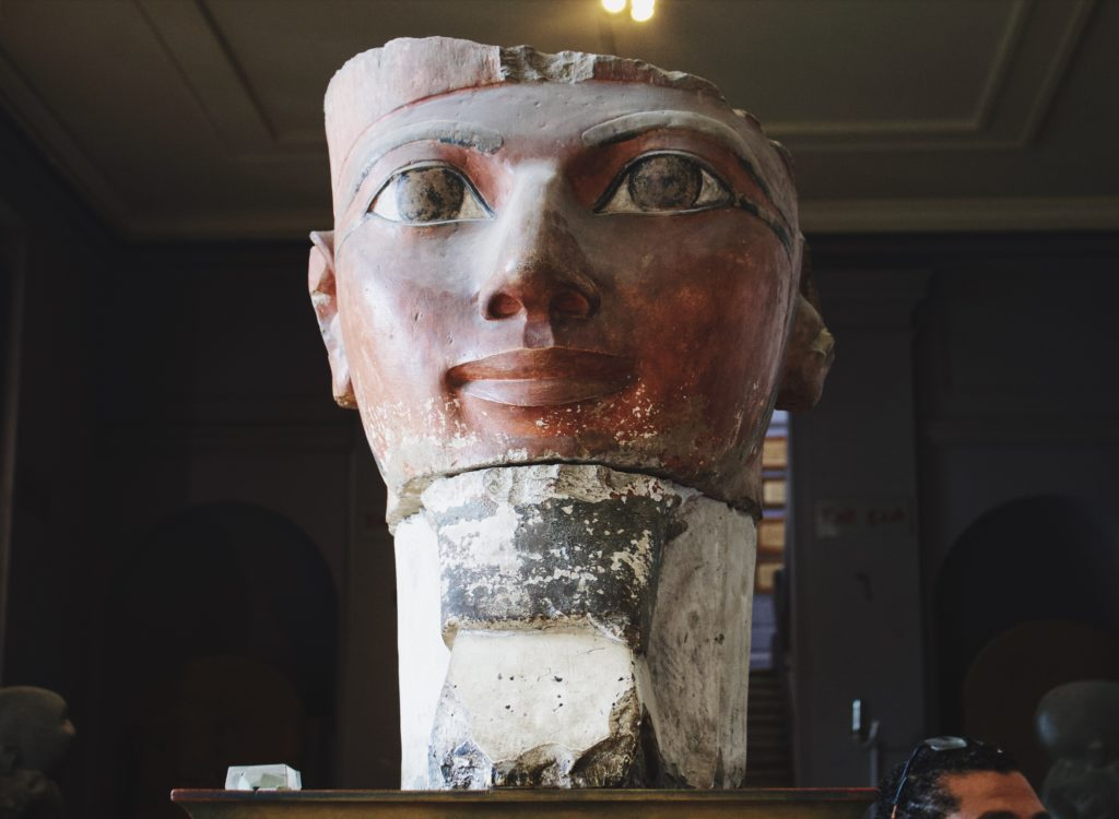 A big head of a statue sitting on a pedestal.